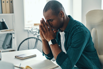 So tired. Frustrated young African man in shirt keeping eyes closed while sitting in the office