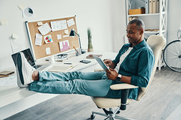 Freelance work. Handsome young African man in shirt using digital tablet and smiling while sitting in the office