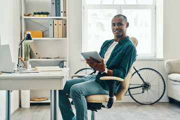 Putting ideas into something real. Handsome young African man in shirt working using digital tablet while sitting in the office