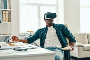 What is real? Handsome young African man wearing virtual reality simulator headset while sitting indoors