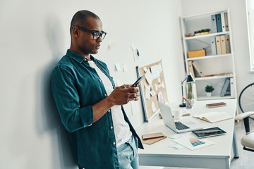 Business is his life. Handsome young African man in shirt using smart phone while standing in the office