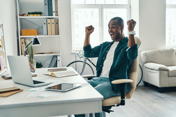 Success! Handsome young African man in shirt cheering and smiling while sitting in the office