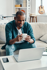 Relaxing at home. Handsome young African man using laptop and smiling while sitting indoors