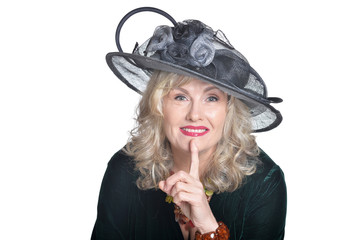 Senior woman wearing black hat with silence gesture on white background