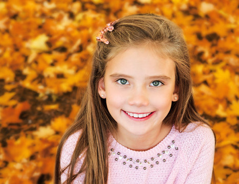 Autumn portrait of adorable smiling  little girl child with leaves