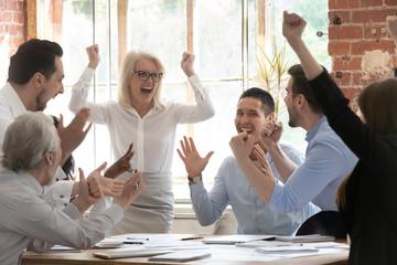 Overjoyed happy corporate business team people scream celebrate triumph