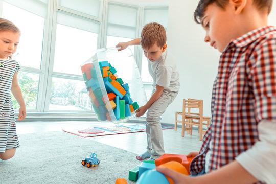 Nice joyful boy holding a box with toys