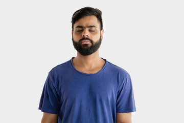 Beautiful male half-length portrait isolated on white studio background. Young emotional hindu man in blue shirt. Facial expression, human emotions, advertising concept. Standing calm with eyes closed Wall mural