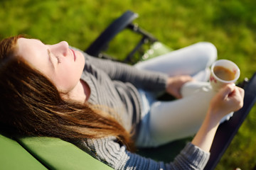 Woman relaxing with closed eyes and cup of coffee in lounge chair on a sunny day outdoors.