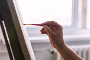 Close up of artist painting in front of window