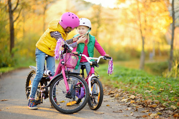 Cute little sisters riding bikes in a city park on sunny autumn day. Active family leisure with kids. Wall mural