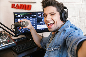 Handsome happy young male radio host broadcasting