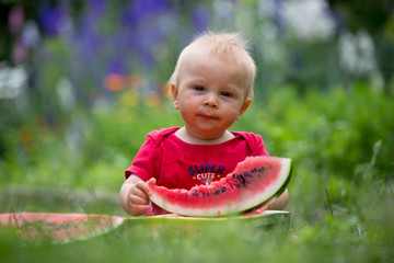 Cute toddler child, baby boy, eating ripe watermelon in garden