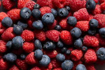 close up view of fresh ripe mixed raspberries and blueberries