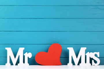 White letters Mr and Mrs with red heart on blue wooden background