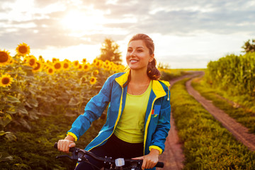 Young happy woman bicyclist riding bicycle in sunflower field. Summer sport activity. Healthy lifestyle Wall mural