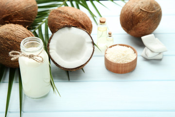 Wall Mural - Coconut milk in bottle with oil and palm leafs on wooden table
