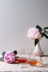 Two glasses of different rose wine standing on grey linen table cloth with pink peonies flowers. Romantic greeting card. Copy space