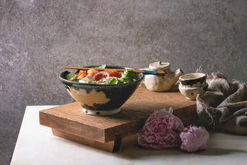 Poke bowl with soy sauce marinated salmon, rice, avocado and tofu cheese served in ceramic bowl with chopsticks, teapot, peonies flowers on japanese wooden serving table over white marble.