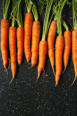 Young carrot with tops in row over black texture background. Flat lay, space. Cooking concept, food background.
