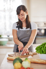 Beautiful smiling dedicated Caucasian brunette in apron standing in kitchen and chopping mushrooms. On table are lots of vegetables. Cooking at home concept.