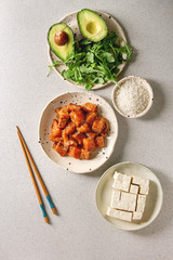 Ingredients for cooking poke bowl. Rice, soy sauce marinated salmon, avocado, tofu cheese and green salad in ceramic bowls served with wooden chopsticks over grey spotted background. Flat lay, space.