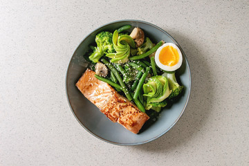 Ketogenic low carb diet dinner grilled salmon, avocado, broccoli, green bean and soft boiled egg in ceramic bowl over grey spotted background. Flat lay, space