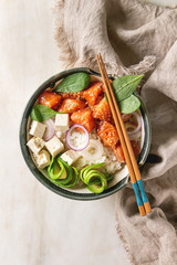 Poke bowl with soy sauce marinated salmon, rice, avocado and tofu cheese served in ceramic bowl with chopsticks over white marble background with linen cloth. Flat lay, space