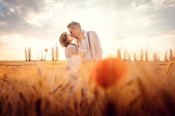 Hochzeitspaar bei der Hochzeit küsst sich in romantischer Stimmung Fototapete