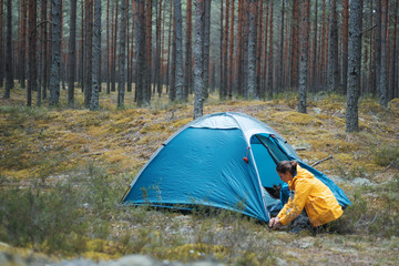 young beautiful woman puts up a tent in the forest, camping, solo travel, nature-nature concept