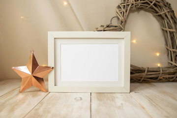 Rustic white Christmas frame mock up on light wooden surface with rose gold copper star, wicker heart and fairy lights - styled creative mock-up