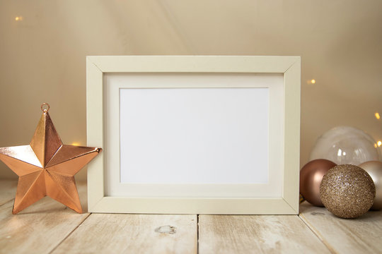 Rectangle poster mock up with cream frame, Christmas baubles, copper star and fairy lights on cream wall background