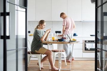 Young wife texting in smartphone by brunch while her husband cooking in the kitchen