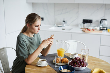 Young attractive woman using smartphone while having breakfast or brunch in the kitchen