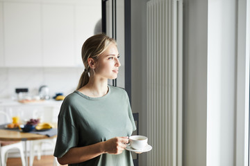 Young casual woman with cup of coffee looking through window while staying at home on weekend