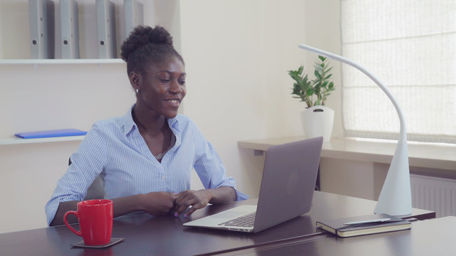 Young businesswoman has video conference call with partner or friend. Afro american manager greeting interlocutor speaking with happy smile using laptop. Cute woman sitting at the working place in