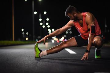 Man preparing to run through the city at night, he stretching his leg muscles.