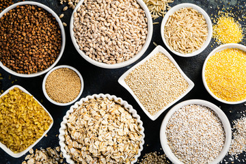 Selection of whole grains in white bowls - rice, oats, buckwheat, bulgur, porridge, barley, quinoa, amaranth on dark background