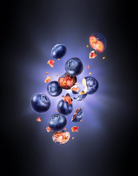 Whole and sliced fresh blueberries in the air with flash of light in the dark