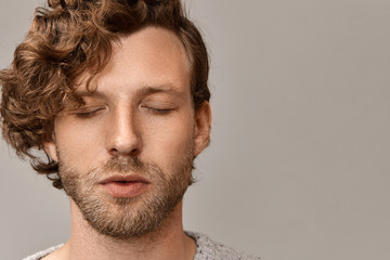 Close up portrait of handsome unshaven young male with stylish hairdo and freckles having peaceful calm facial expression keeping eyes closed, practicing meditation in the morning. Harmony and balance Wall mural