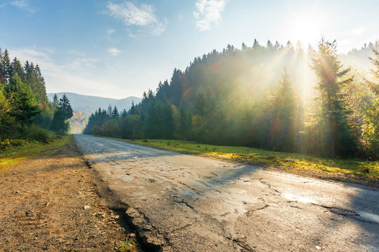 old road through forest in mountains at sunrise. beautiful transportation scenery in autumn. fluffy clouds on the azure sky. cracked asphalt and gravel roadside. sun above the trees
