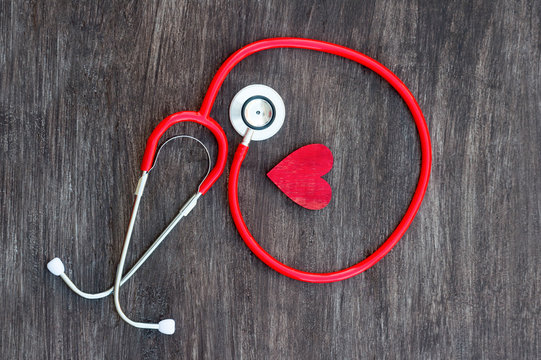 Stethoscope and red heart on wooden background. Health care concept