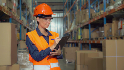Manager female working at warehouse. Attractive young woman worker wearing uniform hard hat and orange vest, counting box for delivery filling up form holding pen.