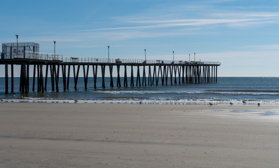 Fishing Pier Over Calm Ocean with Seagulls at Low Tide
