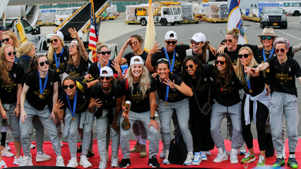 U.S. women soccer players pose for a picture with the Trophy for the FIFA Women's World Cup while the team arrive to the Newark International Airport, in Newark, New Jersey
