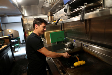 A chef cooks vegan food in the Green Grill section of the Green Vic, which is aiming to be the world's most ethical pub, in Shoreditch, London