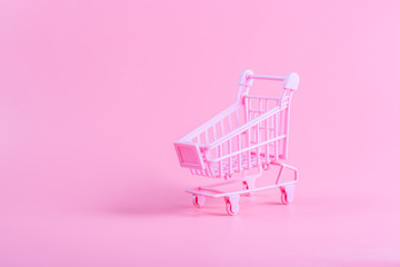 Shopping cart over pink background