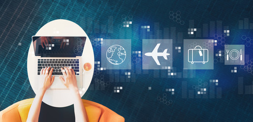 Wall Mural - Airplane travel theme with person using a laptop on a white table