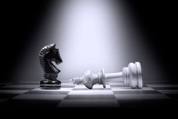 White king chess piece defeating by black knight chess piece