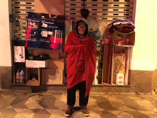 A homeless man covers himself with a blanket as he poses on a street on a cold night in Sao Paulo